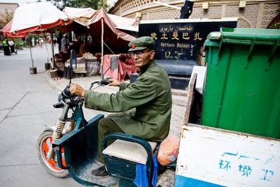 مردی در حال حمل آشغال در کاشگار ، منطقه خودمختار اویگور چین